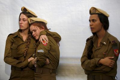 """Soldados israelíes lloran durante un homenaje a los caídos en la operación contra la Franja de Gaza """"Margen Protector"""", de 2014, en la que murieron 63 israelíes y más de 2.200 palestinos, en el cementerio militar del Monte Herzl en Jerusalén."""