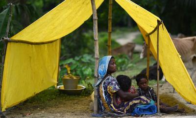 Una madre se refugia con sus hijos en una tienda de campaña provisional tras las inundaciones que afectaron el distrito de Morigaon, en India.