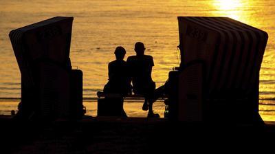 Una pareja sentada frente al mar mientras contempla el atardecer en una playa de Norderney, Alemania.