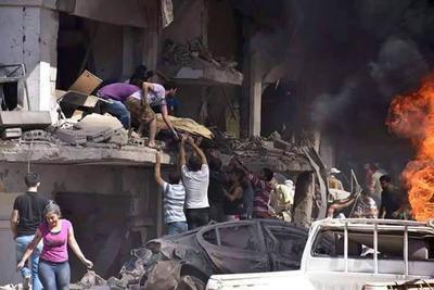 Fotografía facilitada por la Agencia Oficial de Noticias siria, SANA, que muestra a varias personas mientras trasladan un cuerpo tras la explosión de una bomba en Qameshli, Siria.