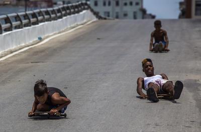 """Niños se deslizan por una pendiente utilizando carros improvisados se conocen como """"chivichanas"""" en el centro de La Habana, Cuba."""
