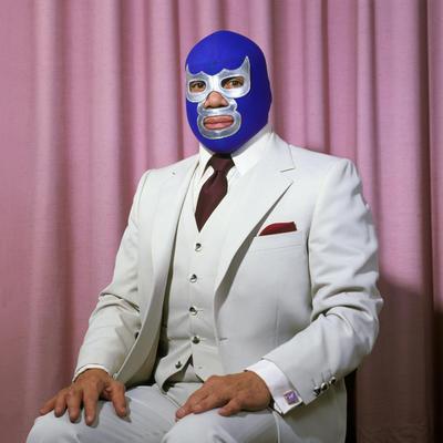 """Imagen titulada """"Blue Sentado"""" de 2005, parte de la serie Lucha Libre la mexicana Lourdes Grobet y que forma parte de la exhibición del Museo de Brooklyn de fotos sobre historia del deporte."""
