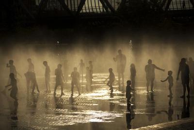 La gente se refresca a sí misma en una fuente pública de agua al lado del río Manzanares durante un día de verano caliente en Madrid.