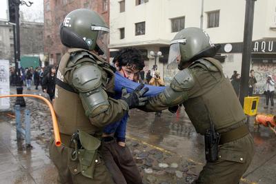 Carabineros detienen a un manifestante durante una marcha no autorizada, en Santiago (Chile).