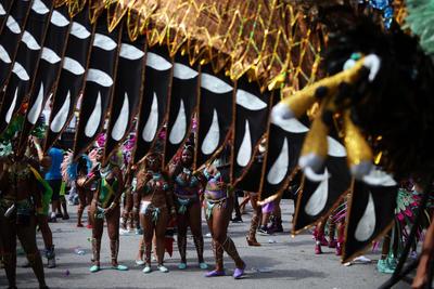 Miembros de un grupo de baile se preparan para el iniciar la ruta del desfile, en el gran desfile del Carnaval del Caribe de Toronto.