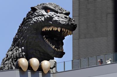 La gente toma fotografías de la cabeza de Godzilla de Toho en Shinjyuku edificio en el distrito de Kabukicho en Tokio Japón.