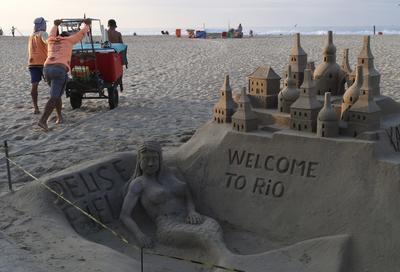 Hombres brasileños empujan su carro con refrescos y asientos a través de la arena cerca de una escultura de arena que da la bienvenida a la gente a Río con una sirena de bienvenida.