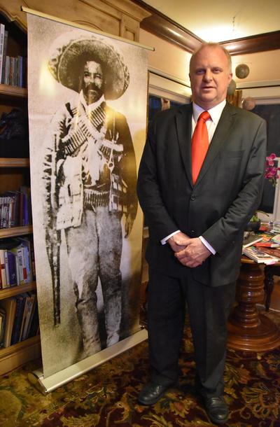 El promotor de arte e historia Gregorio Luke, quien posa junto a un poster gigante de Pancho Villa en su vivienda en Long Beach (Estados Unidos).