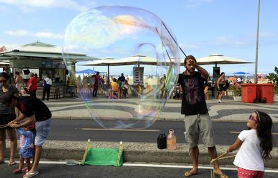 Un hombre hace una burbuja gigante para una niña en la playa de Copacabana, Río de Janeiro, Brasil.
