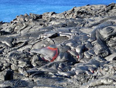 Un folleto  muestra el flujo de lava continua para adentrase en el océano en el flanco sur del Monte Kilauea erupción, Hawaii.