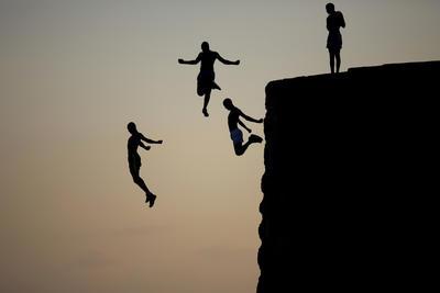 Chicos árabes israelíes saltan en el mar Mediterráneo desde la antigua muralla que rodea la ciudad vieja de Acre, al norte de Israel.