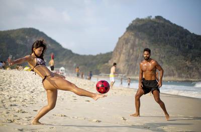 Ana Beatriz, a la izquierda, y Thiago Zaganelli,  patean una pelota en la playa de Copacabana antes de las próximas Juegos Olímpicos de 2016 en Río de Janeiro, Brasil.