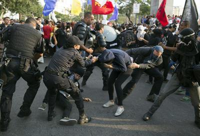 Los manifestantes pelean con la policía antidisturbios durante una protesta contra el dinero gastado en Juegos Olímpicos de 2016 del Río sobre el recorrido de la antorcha olímpica en Niteroi, Brasil.