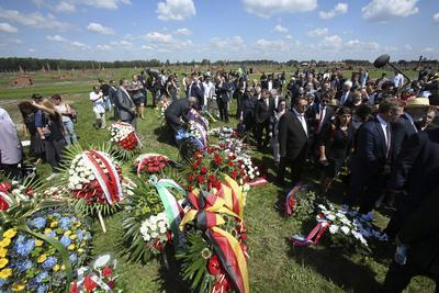 Varias personas depositan flores para rendir homenaje a las más de 500.000 víctimas gitanas del Holocausto nazi en el campo de concentración de Auschwitz-Birkenau en Polonia.