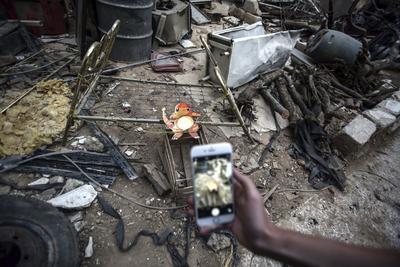 Fotografía, que muestra a un hombre mientras realiza una fotografía con su teléfono a una figura del juego Pokémon Go, en la ciudad sitiada de Duma, Siria.