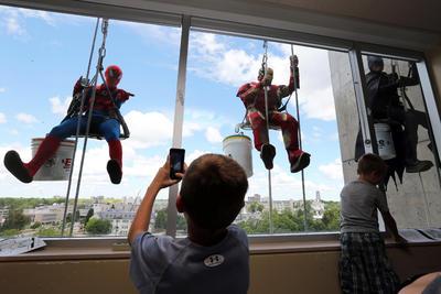 Llimpiadores de ventanas vestidos como súper héroes limpian cristales en el Hospital General de Kingston.