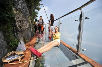 Una turista tomándose una foto en un camino de vidrio elevado en la montaña Panlong en la provincia de Hunan Province (China).