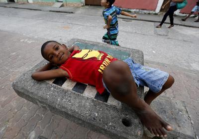 """Un niño descansa en las calles dentro de la """"Ciudad de Dios"""" (Cidade de Deus) una favela que se hizo tristemente célebre por la película del mismo nombre en 2002."""