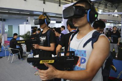 Dos jóvenes prueban unas gafas de realidad virtual (RV) en la feria internacional de la industria de RV de Pekín, China.