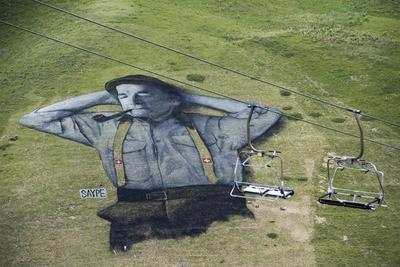 Vista de una imagen que representa a un pastor suizo, hecha con pintura biodegradable, obra del artista francés Saype en 10,000 metros cuadrados de césped en Leysin, Suiza.