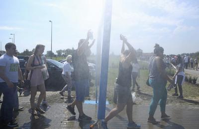 Varios turistas pasan bajo los aspersores de agua en el aparcamiento del Museo Auschwitz-Birkenau en Oswiecim, Polonia.