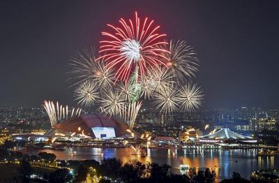 Una imagen de obturación lenta que muestra los fuegos artificiales que estallan sobre el Estadio Nacional (i) y el Estadio Cubierto durante las celebraciones del 51º Día Nacional en Singapur.