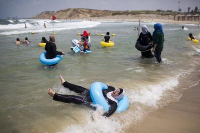 Fotografía, que muestra a varios palestinos disfrutando en la playa de Tel Aviv en Israel.