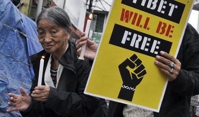 Tibetanos exiliados en India se manifiestan con pancartas que llevan la consigna 'Tibet will be free' (Tíbet será libre) contra la demolición del monasterio Larung Gar por las autoridades chinas en Dharmsala, India.