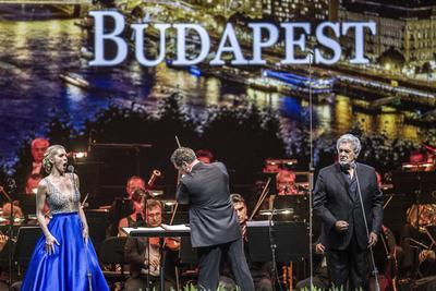 El tenor español Plácido Domingo (d), la soprano estadounidense Micaela Oeste (i) y el director de orquestra Eugene Kohn (c) en escena durante un concierto gratuito en la Arena Papp Laszlo en Budapest, Hungría.