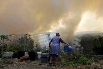 Una mujer riega junto al humo provocado por el fuego declarado en la localidad de Águeda Portugal hoy 10 de agosto de 2016.