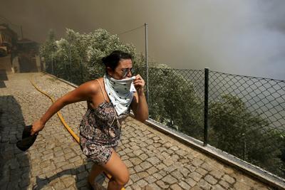 Una mujer huye del humo provocado por el fuego declarado en la localidad de Celadinha, Arouca, Portugal hoy 10 de agosto de 2016.