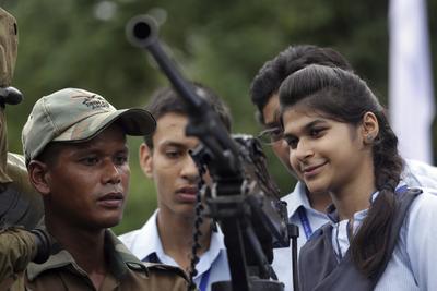 """Un soldado muestra a jóvenes el funcionamiento de un arma de fuego en la exposición """"Conoce a tu ejército"""" en Amritsar (India)."""