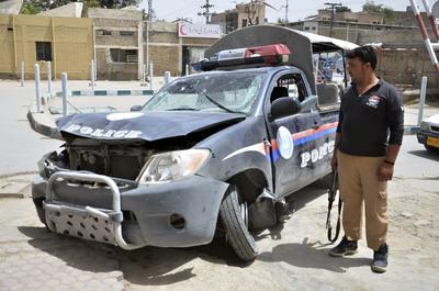 Un agente de seguridad permanece junto a un vehículo policial dañado tras explotar una bomba en Quetta (Pakistán).