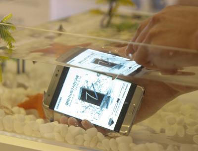 Una mujer prueba Galaxy Note 7, el nuevo tabléfono de la compañía, un híbrido de tableta y teléfono móvil, bajo el agua en la sede de Samsung en Seúl (Corea del Sur).