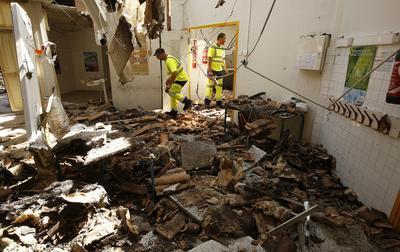 Un par de operarios municipales revisan el estado de una escuela primaria tras el incendio registrado en la localidad de Vitrolles, cerca de Marsella, en el sur de Francia.