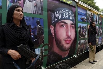 """Varias guardias de seguridad paquistaníes permanecen junto al cartel de Burhan Wani, un líder separatista cachemiro asesinado por las tropas indias en la Cachemira india, mientras protegen el """"Tren Adadi"""" o """"Tren de la Libertad"""" a su llegada a Rawalpindi desde Peshawar, Pakistán."""