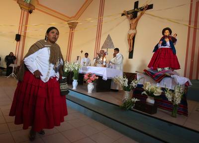 """Indígenas aimaras participan durante la ceremonia religiosa en la el obispo de El Alto, el italiano Eugenio Scarpellini, que da su bendición a la entronización de una inédita escultura de la Virgen María, vestida como una """"cholita"""" aimara de esa región de Bolivia, en El Alto (Bolivia)."""