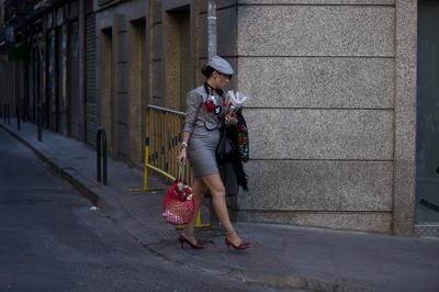 Madrid, España.- Una mujer vestida con ropa de estilo típico de Madrid pasa junto a una motocicleta durante las fiestas de verano Madrid que incluyen bebidas, bailes y procesiones religiosas. (AP)