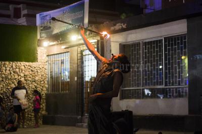 El artista finge comer fuego para después continuar con su performance.