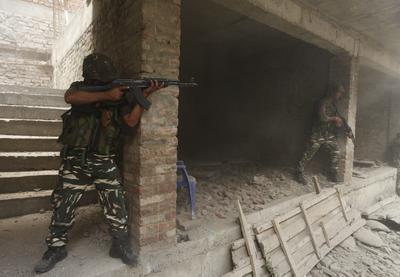 Soldados indios toman posiciones cerca del edificio donde supuestos combatientes se esconden, durante un tiroteo en la zona de Nowhatta, en el centro de Srinagar, capital estival de la Cachemira india.