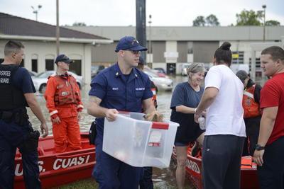 Miembros de la Guardia Costera de Estados Unidos rescatan a varias personas y a sus animales domésticos de una zona inundada de Baton Rouge, ayer domingo.