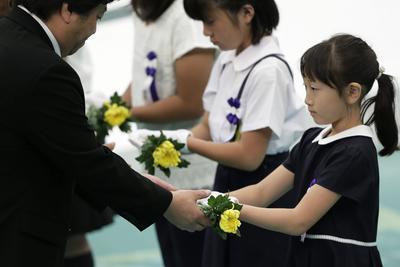 Varias personas reciben flores en memoria de sus familiares fallecidos durante la Segunda Guerra Mundial durante una una ceremonia celebrada en recuerdo del 71 aniversario del conflicto bélico celebrada en Tokio (Japón).