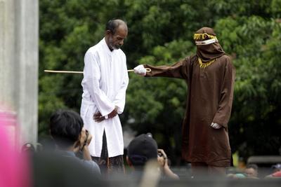 Un hombre recibe latigazos en público por violar la ley sharia en Banda Aceh (Indonesia).