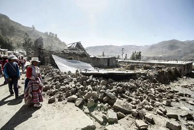 En esta foto proporcionar por la agencia estatal de noticias, Andina , una mujer se ve en las ruinas de su casa destruida por un terremoto en Chivay, Perú.