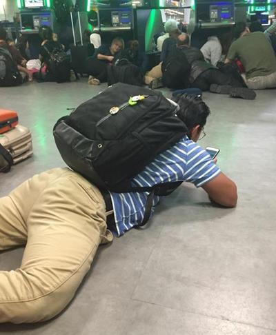 En esta imagen proporcionada por Diana Brooks, los pasajeros que llegan en la zona de control de pasaportes del aeropuerto Kennedy de Nueva York permanecen en el suelo después que las autoridades les ordenaron que se siente  por el temor de posibles disparos.