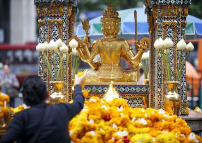 BANGKOK (TAILANDIA).- Un deboto ofrece una guirnalda de flores a la imagen del dios Brahma, el dios hindú de la creación, de cara a las celebraciones por el primer aniversario del atentado contra el templo hindú Erawan, en Bangkok (Tailandia). Una bomba mató a 20 personas e hirió a 125 en el templo hindú, situado en el centro comercial de Bangkok, el 17 de agosto de 2015. EFE