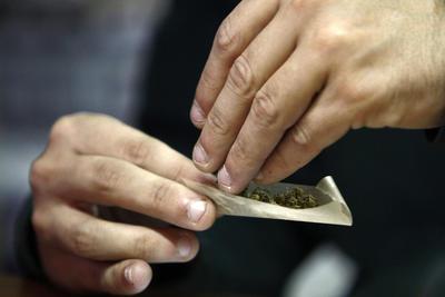 """MONTEVIDEO (URUGUAY).- Fotografía de archivo del 27 de mayo de 2015 de un hombre armando un cigarrillo de marihuana en Montevideo (Uruguay). La venta de cannabis recreativo en unas 50 farmacias de todo Uruguay, un plan piloto previsto por el Gobierno tras la regulación de esa sustancia aprobada por ley en 2013, """"no va a cubrir la demanda"""" que existe """"de acuerdo a las encuestas"""", indicaron hoy, martes 16 de agosto de 2016, a la prensa fuentes oficiales. EFE"""