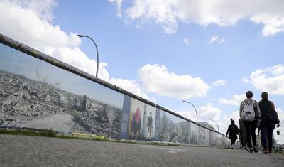 BERLÍN (ALEMANIA).- Varios turistas observan un mural decorado con fotografías de una ciudad destruída de Siria en la galería de arte East Side en Berlín, Alemania. El fotografo Kai Wiedenhöfer presenta sus fotografías tomadas durante la guerra de Siria en la exposición 'War on Wall' (Guerra en la Pared) sobre el antiguo Muro de Berlín. La exposición está disponible hasta el próximo 25 de septiembre. EFE