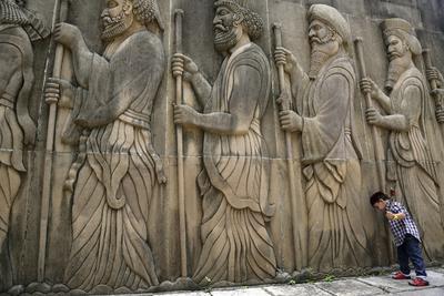 BOMBAY (INDIA).- Un niño parsi o zoroastriano camina delante de un muro esculpido con estatuas de caballeros en el exterior del templo del Fuego durante la celebración de Nowruz, el nuevo año Parsi, en Bombay, la India. Nowruz es el primer día del primer mes del año zoroastriano. Los parsis son seguidores de una antigua religión persa conocida como Zoroastrismo, y viven en su gran mayoría en la India, Irán y Pakistán. El Nowruz es la celebración del equinoccio primaveral y el Khodadsal, el nacimiento del profeta Zaratustra. EFE/Divyakant Solanki