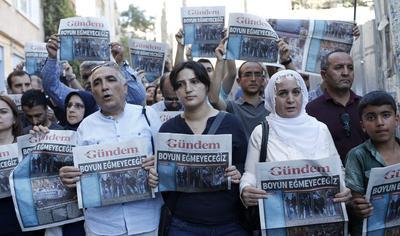 """ESTAMBUL (TURQUÍA).- Varias personas muestran el periódico del diario Özgür Gündem en cuya portada se puede leer """"No nos inclinaremos"""" durante una manifestación en las inmediaciones del rotativo en Estambul, Turquía. Un juzgado de Estambul decretó ayer el cierre """"temporal"""" del diario Özgür Gündem, conocido por su orientación prokurda, bajo la acusación de que """"realiza propaganda a favor del PKK"""", la guerrilla kurda. EFE"""